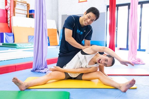股関節を伸ばす開脚を行う持永さん。仙田コーチにアシストしてもらいながらじっくり時間をかけてストレッチ