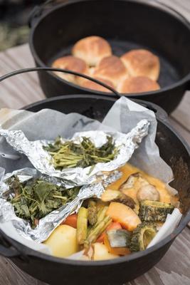 ダッチオーブンで仕上げた「温野菜のラクレットチーズ」(手前)、「自家製の丸パン」(奥)