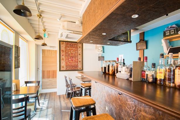 """インドのタペストリーが目を引く、アジアンチックな店内。テーブルのほか、カウンターも6席あり、夜は""""ひとり呑み""""の客も多い"""