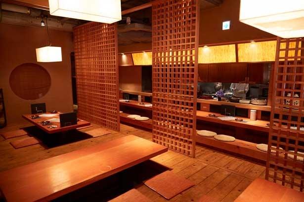 【写真を見る】格子戸がおしゃれな掘りごたつ式のテーブル席。カウンター席もあり、オープンキッチンの様子が間近に見える