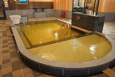 源泉風呂。鉄の成分が多いことから、褐色がかっているのが特徴/天然温泉アーバンクア・大浴場