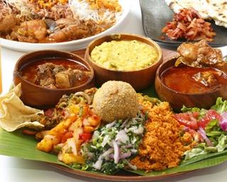 右からチキン、豆、日替りカレー3種。山盛りになっているさまざまなおかずの下にはご飯が。上にのっている丸いものは、スリランカのコロッケ「カトゥレット」