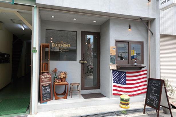 「ALL HOME MADE」と書かれたサインボードとアメリカの国旗がお出迎え。バーガーは右の小窓からテイクアウトもできる/DEXTER DINER