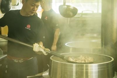 久留米 大砲ラーメン 本店 /スタッフの小川将仁さん。呼び戻しスープ作りは、その日の豚骨の状態や気温、湿度などに左右されるため熟練の技を要する