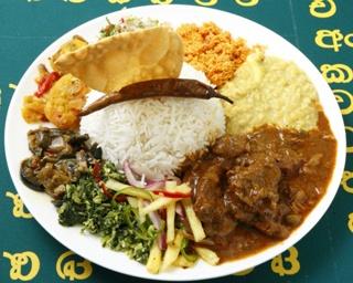 「チキンカレー」(900円)。水菜のサラダ、パイナップルのサラダ、小松菜の炒め物、タマネギの炒め物、ココナッツサンボルなどが入っていて、とっても良心的な価格になっている