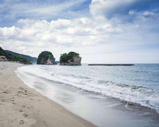 「西方海水浴場」。遠浅のビーチで、引き潮の時は浜辺の奥行きが200mになることも。海水浴場の両側に海の家がある
