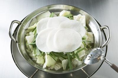 【写真を見る】餃子の皮がのった、あっさりもつ鍋!「もつ鍋専門 もつ幸」の「もつ鍋」(写真は3人前3000円)は、鶏ガラスープを使い、餃子の皮がのるのが特徴