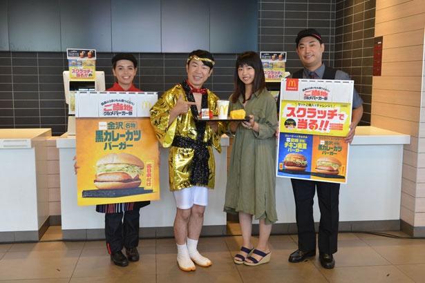 【写真を見る】女性客に「金沢名物黒カレーカツバーガー」を手渡し、記念撮影に応じるダンディ坂野