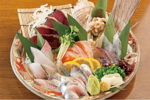 【写真を見る】「魚たま名物 刺身盛り合せ」(1,058円)は、カツオやツブ貝、カンパチなどその日の魚介類約7種