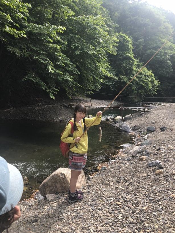 魚を釣り上げ、笑顔を見せる内田珠鈴