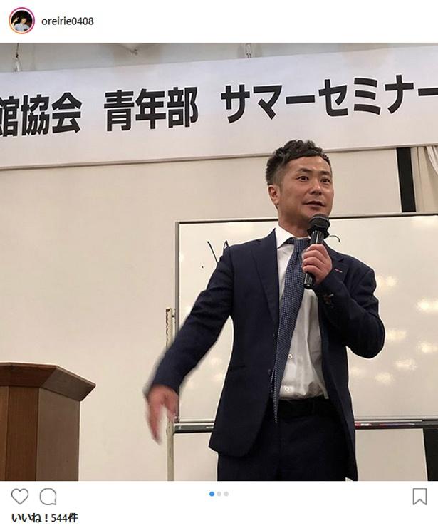 【写真を見る】マイクを持ち講演活動を行う入江慎也