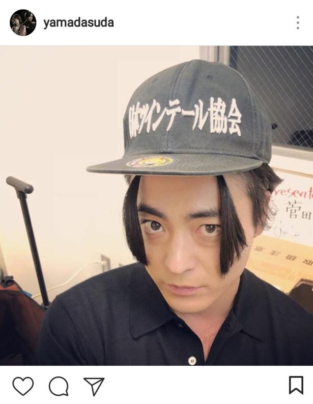 「日本ツインテール協会」と書かれた帽子をかぶりポーズを取る謎の山田孝之
