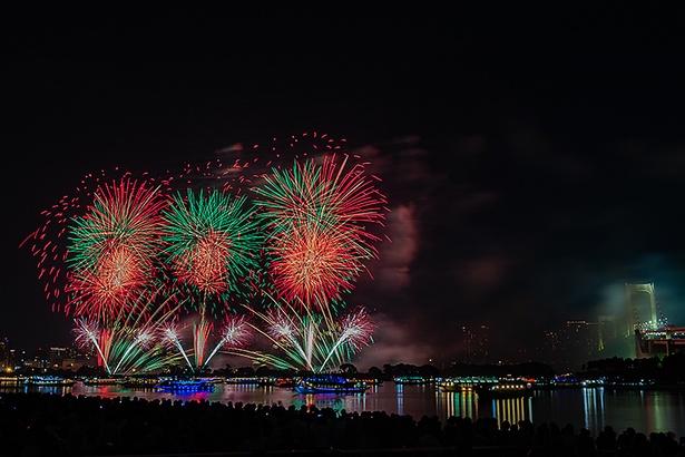 屋形船の光と花火で東京湾が明るく照らし出される