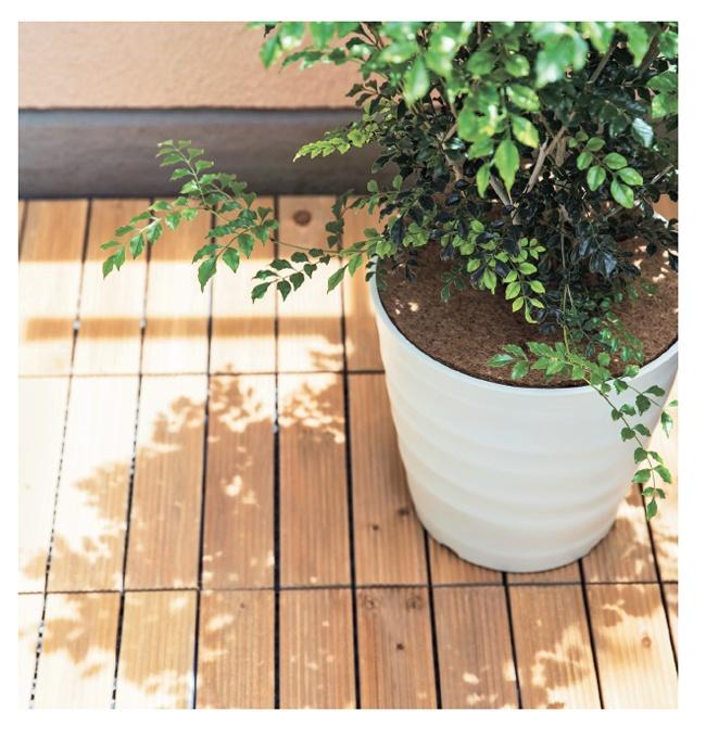 コンクリートのベランダはウッドパネルや植木で影をつくって