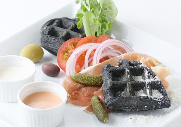 【写真を見る】「KURO=ワッフルの生ハムオープンサンド」(2200円)。黒いクロワッサンワッフルに、生ハムや野菜、オリーブを添えた。アクセントにはパルメザンチーズも!