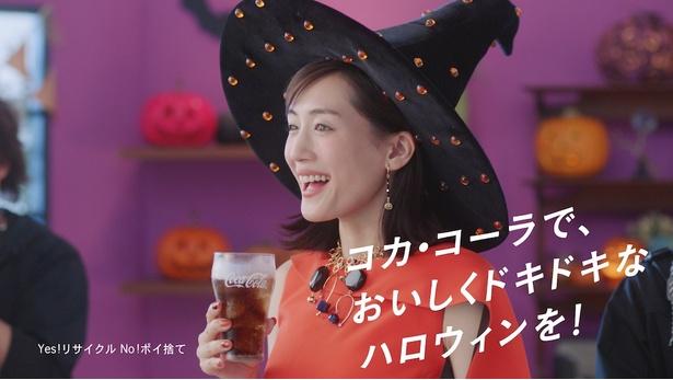 オレンジのワンピ ースに黒い帽子を合わせた魔女ルックでコカ・コーラを飲む綾瀬