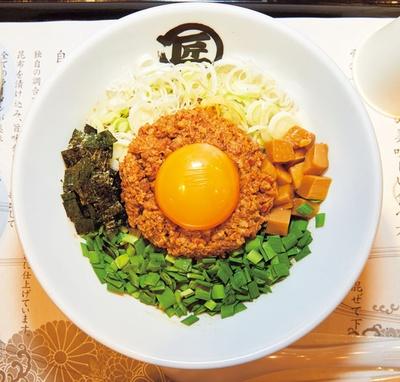 【写真を見る】台湾まぜそば(780円)。自家製の台湾ミンチ、ニラ、白ネギ、刻みメンマ、卵黄などの具材がどっさり!/麺や マルショウ