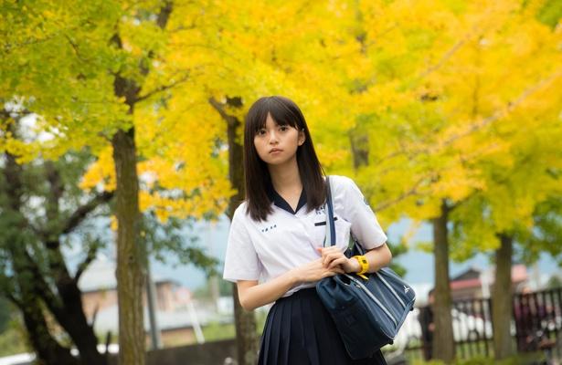 白の開襟ブラウスに濃紺のプリーツスカートという優等生的制服姿