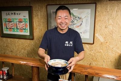 看板メニューの「こく煮干し」(850円)を差し出す店主の長尾大さん。「青森独特の煮干しラーメンをお楽しみください」