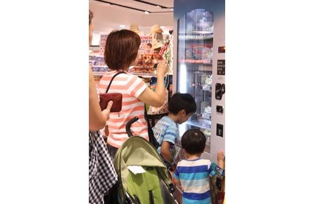 バナナ自動販売機の珍しさに、記念に写真を撮っている様子