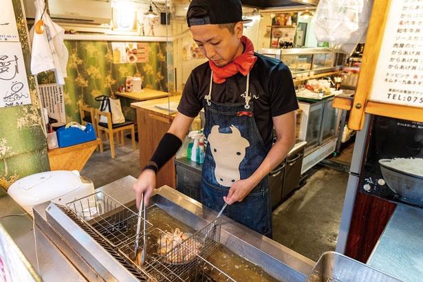 ひっきりなしに揚げ物を油に入れる村田さん/京都串焼きホルモン 梅しん