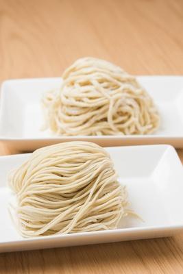 麺は細ストレート(手前)が基本だが、+50円で平打ち(奥)に変更できる
