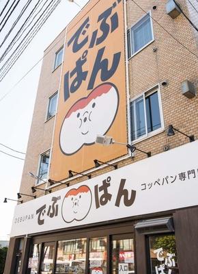 地下鉄南北線・麻生駅4番出口の道路を挟んで向かいに建つビルの1階に店舗がある。ビル外壁の大きな看板がとにかく目立つ!