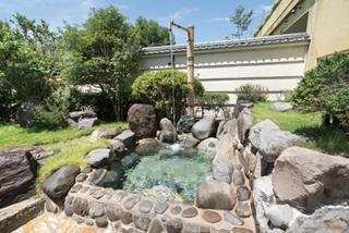 打たせ湯を備えた大浴場の露天風呂。周りに植栽された緑がまぶしい