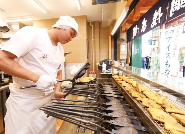 熟練の職人が1丁2㎏の焼き型を巧みに操って鯛焼きを焼き上げていく。火床の上でガチャガチャと焼き型を回す様子は圧巻だ