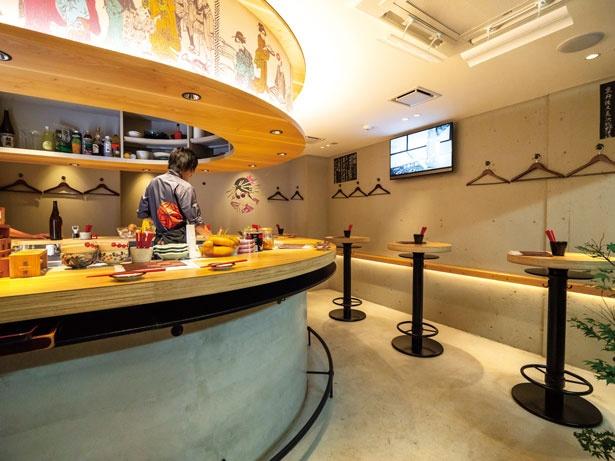 カーブを描く木のカウンターや、和のテイストを取り入れたポップなイラストが印象的な店内/京都立呑 きよきよ