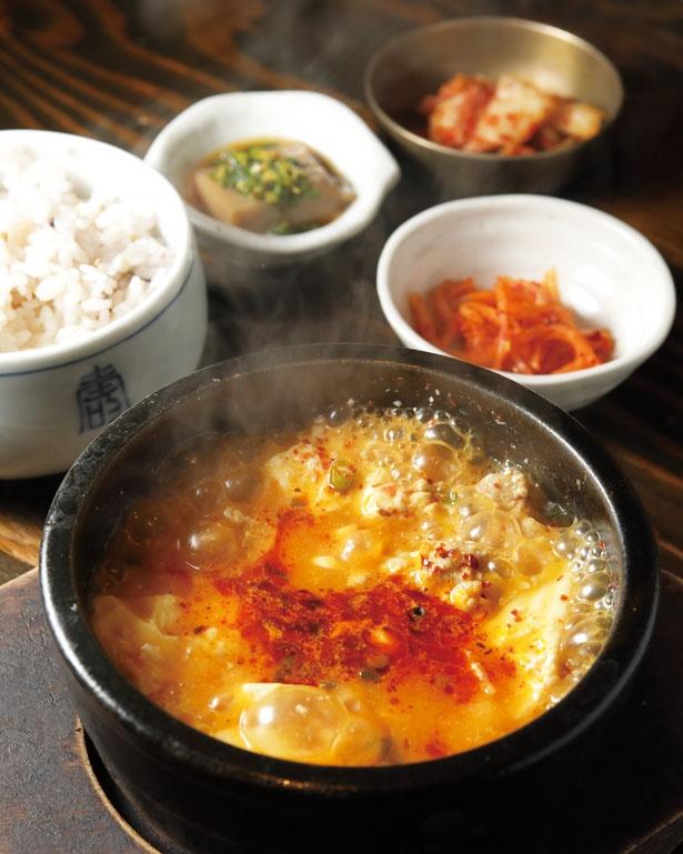 おぼろ豆腐、アサリ、豚肉のあっさりスープに、日替りのおかず3品と十六穀米が付く「スンドゥブ定食」(1100円)/ピニョ食堂