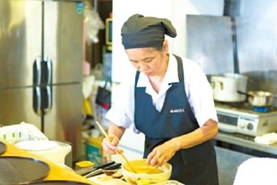 厨房で手際よくラーメンを作る女将の八重子さん。食後にコーヒーがサービスされる