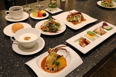 ランチコースで供される料理メニュー。オードブル、温かい前菜、サラダ、スープ、パン、魚料理、肉料理、デザート、ドリンクの全8品