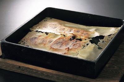 博多鉄鍋 参の三の、博多鉄鍋一口餃子(12個入)…580。一つ一つ店で手作りで提供される餃子は、外はパリッと、中はモチッとした食感を楽しむことができる。店独自の甘いポン酢と、ユズコショウで食べるのがおすすめ
