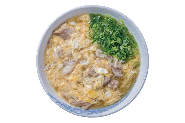 【写真を見る】弥太郎うどん / 「親子うどん」(580円)。ふわふわの卵と鶏肉が麺をおおう。スープは透明度の高い黄金色で、香り高い魚介のダシが卵に染み込む