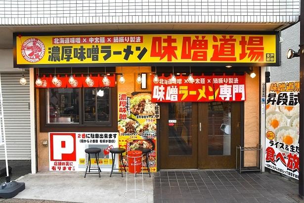 黄色と赤を基調にした派手な外観が目をひく。店内はPOPやポスターがあちこちに張られインパクト大「濃厚味噌ラーメン 味噌道場 戸田支部」
