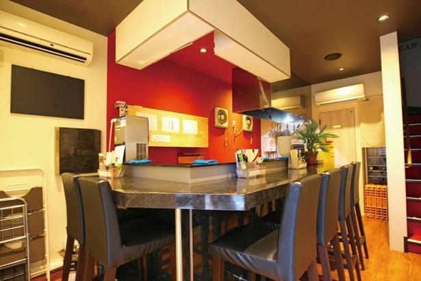 赤い壁が印象的な店内。カウンター席はゆとりの配置で、片隅にはカップル専用席も設けられている