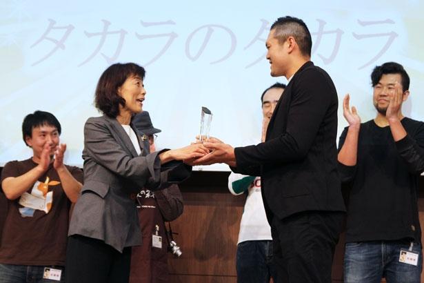 審査委員長の本間るみ子氏(左)から、グランプリのトロフィーを授与される、チーズ工房タカラの斉藤愛三さん(右)