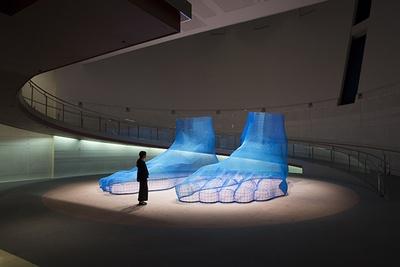 【写真を見る】日本の農耕現場で獣害対策に使用される金網やネットを素材とし、農民の労働と生産へのオマージュとして制作した作品に光を加えた「海足/Pacific Feet」。象の鼻パークに設置