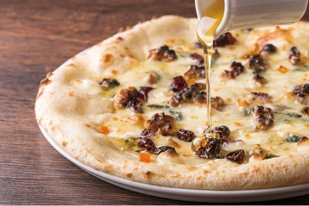 ゴルゴンゾーラとドライフルーツ、ハチミツの甘じょっぱいおいしさが楽しめる「クルミとブルーチーズのピザ」(1,620円)