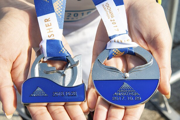 左が2018年のメダル。カモメをモチーフに、みなとみらいの街並と青い海をデザイン。右は幻となった2017年のメダル。どちらもずっしり重量感あるアイテムだ