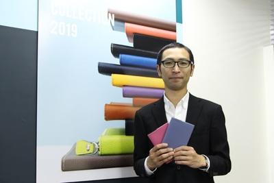 クオバディス・ジャパン セールス&マーケティンググループ チーフの増田良之さん。手に持っているのは、新色のスモーキーカラーが加わった、合皮カバー「ソーホー」