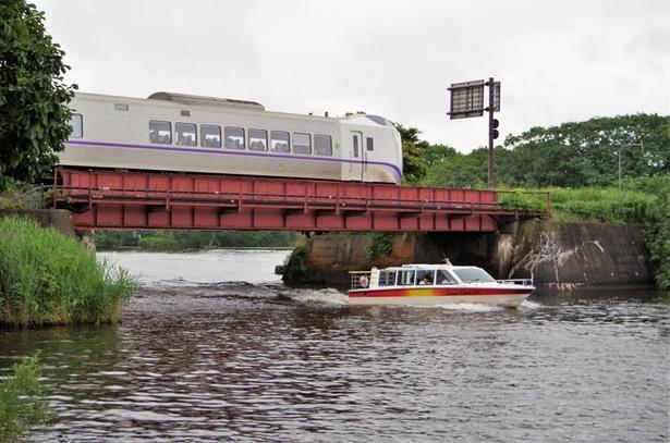 大沼公園の大沼湖と小沼湖の間をボートが走り抜け、その真上の鉄橋を特急列車スーパー北斗が駆け抜けます(大沼公園駅~赤井川駅間)