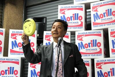 「M@福袋(3,000円)」の中身を、自ら解説する森村氏。直筆の顔が描かれた皿などレアなアイテムも!
