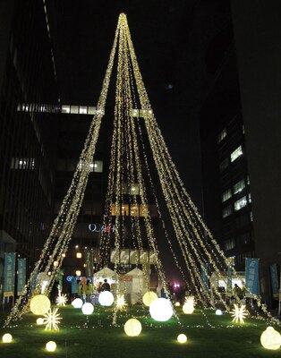 福岡銀行本店 / シャンパンゴールドの光のタワーを囲むように、大小さまざまな光が緑の中にちらばる。ピンクリボン運動の一環で、今年はピンク色のイルミも登場