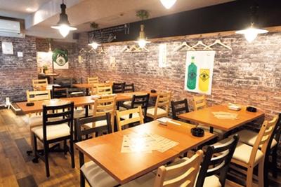 レンガ風の壁が印象的な、落ち着いた雰囲気の店内はテーブル席が中心/ビストロ酒未来