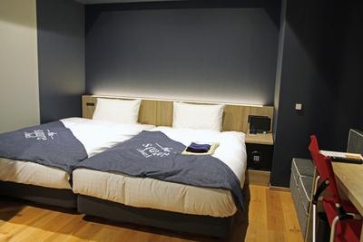 スタイリッシュな中にも木の温もりが感じられ、居心地の良い空間が広がる客室。写真は1200mmのベッド2台を並べて配置した「デラックスツイン」(1室1万3000円~)