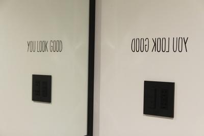 壁に書かれた文字が鏡に映り、反転すると「YOU LOOK GOOD」と読めるようになっている