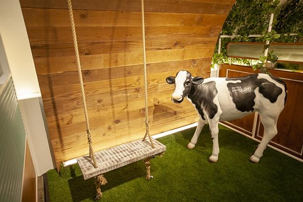 牛とブランコが牧歌的なフォトスポット。記念に写真撮影して帰るお客さんも多い