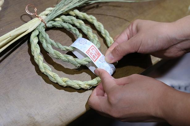 初級コースでは、まずだいこく締めと呼ばれる出雲地方伝統の小型のしめ縄を作る。そこから丸めて輪じめを作り、好みの短冊にスタンプを押して巻き付ければ完成だ